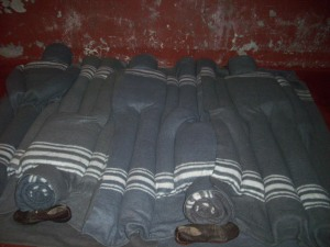 Blanket sculptures of black male prisoners sleeping.