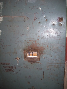 The inside of the door to one of the isolation cells, covered in graffiti left by its inhabitants.