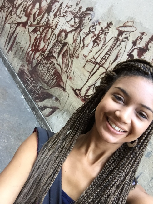 Ariel in front of a mural in Rio